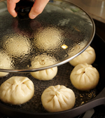 <b>焼く</b> フライパンにサラダ油小さじ1を中火で熱する。肉まんを間隔をあけて並べ、焼き色がつくまで4~5分焼く。水3/4カップを注ぎ、ふたをして水分がなくなるまで8分ほど蒸し焼きにする。ふたを取り、水分がなくなるまで焼く。好みで酢じょうゆ適宜をつけていただく。