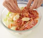 <b>レンジで加熱し、仕上げる</b> 口径23cmの耐熱のボールにキャベツ、ピーマンを入れ、サラダ油小さじ1をまぶして混ぜる。豚肉とねぎをのせ、ふんわりとラップをかけて、電子レンジで7分加熱する。取り出してよく混ぜ、器に盛る。