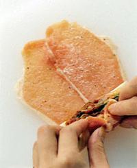 チーズは半分に切る。キムチは汁けをきる。まな板に豚肉1枚を縦に広げ、もう1枚を端が重なるようにして並べる。表面に塩、こしょう、小麦粉各少々をふる。手前の端にチーズ1切れとキムチの1/4量をのせ、向こう側までぎゅっと巻いていく。巻き終わりをしっかりと手で押さえて留め、全体に小麦粉を薄くまぶす。残りも同様にして、合計で4個を作る。   ☆ポイント 豚肉は端を2cmほど重ねて並べます。肉からはみ出さないようにチーズとキムチをのせ、端からぎゅっと巻いていけば、焼いている途中でチーズが溶け出したり、形がくずれることもありません。