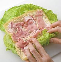 まな板にキャベツ2枚を少しずらしてのせ、油揚げ1枚を重ねる。豚肉の1/2量を広げて、塩、こしょう各少々をふり、手前からひと巻きする。左右の葉を折り込んで向こう側まできっちりと巻き、巻き終わりに半分に折ったスパゲティを刺して留める。もう1つも同様にする。