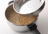 圧力鍋に水4カップと塩、【3】を入れ、ふたに大豆がつかないよう、鍋に付属の蒸し器を落としぶた代わりにのせる。