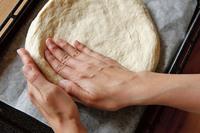 オーブンを200℃に予熱する。オーブンの天板にオーブン用シートを敷いて生地をのせ、手で直径約23cmの円形にのばす。縁を残してへこませ、幅1.5cm、高さ2cmほどの「みみ」を作る。オリーブオイルを薄く塗り、オーブンの下段で10分ほど焼く。