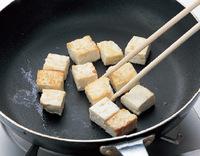 フライパンにサラダ油小さじ1を中火で熱し、豆腐を並べ入れる。焼き色がついたら裏返し、表面を色よく焼いて取り出す。同じフライパンにサラダ油小さじ1を再び中火で熱し、鶏肉を皮目を下にして並べ入れる。焼き色がついたら裏返し、色よく焼いて取り出す。  ☆ポイント 豆腐はフライパンであらかじめ焼きつけると、水っぽくならず、形もくずれにくくなります。