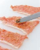 豚肉をまな板に縦長に並べ、みそ大さじ2を等分にまんべんなく塗る。豚肉の手前にいんげんを4~5切れほどのせ、手前から巻く。