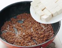 フライパンにサラダ油小さじ1を中火で熱し、ひき肉を木べらでほぐしながら炒める。ぱらりとしたらねぎとしょうがを加えて炒め、香りが立ったらAを加えてなじませる。水1カップを加えて溶きのばし、豆腐を加えて弱火にし、5分ほど煮る。片栗粉小さじ1/2を水大さじ1で溶いて加えてとろみをつけ、枝豆を加えて1分ほど煮る。   ☆ポイント 煮ている間に豆腐から水分が出てくるので、最初に肉みそをしっかりと炒め、濃いめに味つけしておきます。