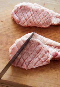 豚肉は赤身と脂身の間に4~5カ所切り目を入れ、筋を切る。包丁の背で、格子状に片面20回ずつ、両面をまんべんなくたたく。