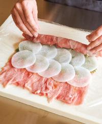 まな板にラップを広げ、豚肉を縦長に少しずらしながら重ね、22×20cmくらいに広げて小麦粉小さじ1/2をふる。奥を1/3残してオイスターだれ小さじ1を塗り広げ、青じそ、大根の順に重ねて並べる。手前のラップを持ち上げて巻きはじめ、全体を押さえながらくるくると巻く。表面に小麦粉小さじ1/2をふる。