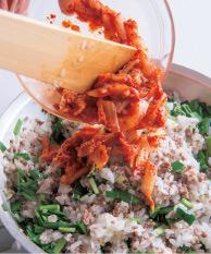 にらを加えて混ぜ、白菜キムチを飾り用に少し取り分けて、フライパンに加える。酒大さじ1をふり、しょうゆ小さじ1を回し入れて炒め合わせる。目玉焼きをのせて飾り用のキムチをのせ、白ごまをふる。