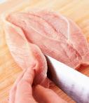 鶏肉はペーパータオルで水けを拭き取る。縦長に置いて、中央に縦に1本切り込みを入れ、切れ目から包丁を寝かせて入れ、片側ずつ外に向かって少しずつ切り込みを入れて開く。鶏肉の皮目全体にフォークで穴をあける(鶏肉が破裂するのを避ける)。