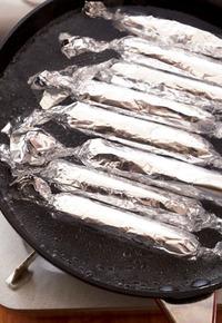 直径26cmのフライパンに湯を沸かし(ソーセージが半分浸るくらいが目安)、ソーセージを並べ入れる。小さな泡が出る程度の弱めの中火で、一度上下を返しながら7~8分ゆでる。ホイルごとざるにあけ、粗熱をとる。完全にさめたらホイルとラップをはずし、新しいラップでぴっちりと包む。冷蔵庫で3~4日間保存可能。食べるときはオリーブオイル小さじ1を中火で熱したフライパンで、1分30秒~2分、ころがしなら焼き、粒マスタードとあればクレソンを添えて。