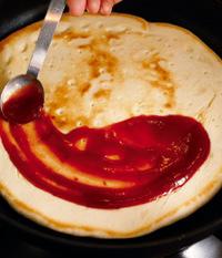 ふたを取って裏返し、弱火にする。ケチャップソースをスプーンの背で塗り広げ、具をバランスよくのせてチーズを散らす。チーズは生地の外側にも散らす。こうすると羽根ができる。
