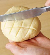 ナイフでごく浅く格子状の跡をつけ、グラニュー糖を全体にふる。オーブンの天板にオーブン用シートを敷き、メロンパンを並べる。170℃のオーブンで10分ほど焼き、アルミホイルをかぶせてさらに5分焼く。
