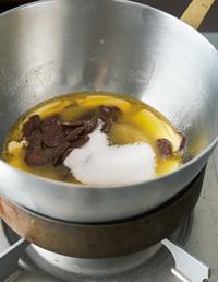 フライパンに湯を沸かし、火を止める。耐熱のボールにチョコレート、バター、グラニュー糖を入れ、ボールの底を湯に当てる(湯せん)。チョコレートとバターが溶けてなじんだら、ボールを湯からはずす。