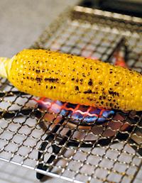 ガス台に焼き網をのせ、とうもろこしを置く。強火にかけ、全体に焼き色がついたら火を止め、粗熱を取る。  ※やけどに注意して。返すときは、トングなどを使うようにしてください。