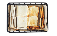 オーブンの天板にオーブン用シートを敷き、パンとみみをのせ、バター20gをパンの表面に薄く塗る。200℃のオーブンで8~10分焼き、そのままさます。