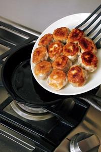 2分ほど蒸し焼きにしたらふたを取り、皿をかぶせて手で押さえ(油がたれることがあるので注意)、スキレットごと返して皿にのせる。スキレットに戻し入れ、ごま油小さじ1を加えて2分ほど焼く。ラー油、しょうゆ各適宜をつけて食べる。