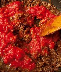 ひき肉を加え、5分ほど炒め合わせる。肉から出た脂が透明になったら、カットトマトを缶汁ごと加え、ときどき混ぜながら5分ほど煮る。火を止め、ルウを加えて溶かし、再び中火にかけて2~3分煮る。器にご飯を平たく盛り、カレーを中心にかける。ゴムべらで表面をならし、卵黄をのせる。