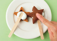 耐熱皿にクッキーを裏側を上にしてのせ、板チョコ1かけ、マシュマロ1切れずつをのせる。ラップをかけずに電子レンジで10秒ほど加熱し、マシュマロが溶けたら取り出す。市販の木製スティック(アイス用)をのせ、もう1枚のクッキーをのせてくっつける。