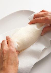 熱いうちにペーパータオルをかぶせ、両端をかるくつまむようにして形を整える。もう1個も同様に作り、それぞれにトマトケチャップ適宜をかけ、ベビーリーフを添える。
