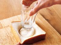 食パンに口径7.5cm前後のコップの口を押しつけて回すように丸く跡をつけ、内側をコップの底で押しつぶす。ここが具を入れる「くぼみ」になる。
