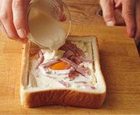 【2】で作ったくぼみにソースの1/2量を流し入れ、卵を割り入れる。卵をおおうようにハムを散らし、残りのソースを加える。アルミホイルを敷いたオーブントースターの天板にのせ、500Wで5~7分、焼き色がつくまで焼く。器に盛って粗びき黒こしょう少々をふる。