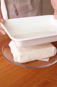 豆腐は厚手のペーパータオルで包んで耐熱皿にのせ、ラップをかけずに電子レンジで1分30秒加熱する。バットや平皿などをのせて重しをし、20~30分おいてしっかりと水きりする。