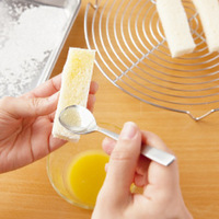 グラニュー糖をバットに広げる。小さめの耐熱の器にバターを入れ、ラップをせずに電子レンジで30~40秒加熱する。パン1個の全面にバターを塗り、バットに移してグラニュー糖を全面にまぶしつける。残りも同様にする。
