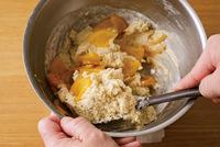 ゴムべらに持ち替える。ふるった粉類を加え、底から返すようにして粉けがほぼなくなるまで混ぜる。【1】のオレンジの1/2量を加え、生地につやが出るまで、底から返すように5~10回混ぜる。  ※粉類を加えたあとは、少し粉けが残るくらいで手を止めてOK。上部と底部を入れ替えるイメージで混ぜて。