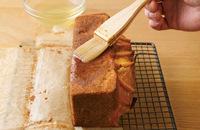 取り出してオーブン用シートごと型からはずし、ケーキクーラーなどにのせる。熱いうちにシートをはがし(やけどに注意)、すぐに全面に1のオレンジの煮汁1/2カップほどを刷毛(なければスプーン)で塗ってしみ込ませる※。粗熱が取れたら食べられるが、1日おくとよりしっとりしておいしい。  ※残った煮汁は炭酸水などで割って飲むのがおすすめ。