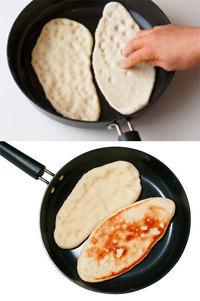 フライパンに油をひかずに、生地2枚を並べ入れる。生地の表面全体を指で押しつけてくぼませながら、形を整える(写真・上)。  ふたをして強火にかけ、30秒ほど焼く。弱めの中火にし、4分ほど焼いて裏返す(写真・下)。ふたをせずにさらに4分ほど焼き、熱いうちにバターを塗る。残りの2枚も同様にする。   〈焼いたナンは冷凍できます〉 1枚ずつラップで包み、密閉できるファスナーつき保存袋に入れて冷凍します。食べるときは自然解凍(または電子レンジで1分加熱)し、オーブントースターで3~4分焼いて。  〈発酵は「一時停止」できます〉 冷蔵庫へ入れれば、発酵を2~3時間ストップできます。再び作りはじめたいときは袋ごと室温に取り出し、残りの発酵時間+5~10分おいて。