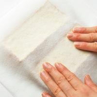 厚揚げは厚みを半分に切り、厚手のペーパータオルではさんで押さえ、余分な油と水けを取る。