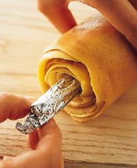 8~10回巻いて、ボールの生地がすべてなくなったら焼き終わり。フライパンから取り出して5分ほどおき、粗熱が取れたら、ラップでぴっちりと包む。完全にさめたら、しんを回しながら引き抜き、端を1~2cmずつ落として、食べやすく切り分ける。ラップで包み、室温に置けば、3日ほど保存できる。