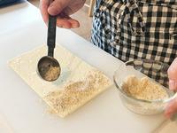 まな板にパイシートを横長に置き、溶き卵を刷毛(またはスプーンの背)で薄く塗る。「S&B スパイス&ハーブ ポピーシード(けしの実)」、粉チーズを混ぜてから全体にかけ、手でかるく押さえる。