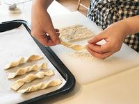 長い辺を10等分にするように帯状に切る。1切れずつ2回ほどやさしくねじり、オーブン用シートを敷いた天板に間隔をあけて並べる。オーブンの下段に入れ、200℃で焼き色がつくまで8~10分焼く。