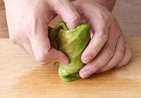 キャベツの葉はキッチンペーパーで水気をふき、1枚ずつ軸を手前にしてまな板に広げる。【3】の肉だねを軸よりやや右手前に置き、手前から一巻きし、葉の左側を内側に折る。そのまますき間なく最後まで巻く。右側を上にしてロールキャベツを立てて、余った葉をすき間にきゅっと詰め込む。残りも同様に、12個作る。
