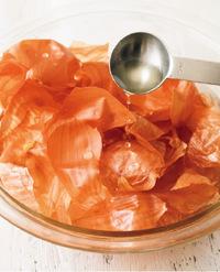 ボールに玉ねぎの皮を入れ、かぶるくらいの水(分量外)を注ぐ。酢を加え、手でかるくもみながら洗い、ざるに上げて水けをきる。酢は皮の殺菌だけでなく、うまみをプラスする効果もある。
