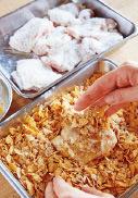 ころものコーンフレークをバットに入れ、もんで粗く砕き、残りの材料を加えて混ぜる。【1】の鶏肉の汁けをきって小麦粉適宜をまぶし、余分な粉をはたき落とす。1切れずつ溶き卵にくぐらせてバットに入れ、手で押さえてしっかりところもをまぶす。