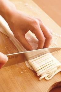 生地をまな板にのせ、端から幅6~7mmに包丁で切る。バットに入れて打ち粉をふり、ちぎれないように全体をやさしくほぐす(打ち粉がたりなければ途中でふる)。ラップでぴっちりと包んで密閉できる保存袋に入れ、冷蔵庫で1週間保存可能。