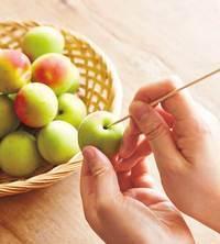 梅は竹串でひっかけるようにしてへたを取り除く。竹串で実を傷つけないよう注意。