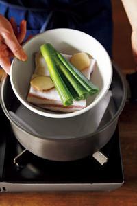 口径22~24cm、深さ10cm以上の鍋にふきんを敷く。豚肉のラップを取り、汁けをしっかりと拭いて長さを半分に切る。鍋よりふたまわりほど小さい耐熱のボールに脂身を上にして入れ、ねぎの青い部分と、しょうがをのせて酒をふる。ボールごと鍋に入れる。
