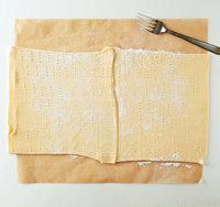 切ったオーブン用シートに打ち粉をかるくふり、パイシートをのせて、1枚ずつめん棒で厚さ2mmくらいにのばす。パイシートの端を1cmずつ重ね、めん棒で押さえながらつなぎ合わせる。フォークでまんべんなく穴をあける(この時点で横幅がオーブン用シートよりやや長くなればOK)。