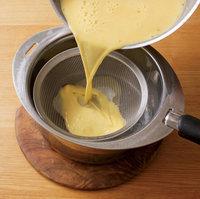 牛乳が入っていた鍋に、【3】のプリン液をざるを通してこしながら戻し入れる。  ※ざるで一度こすと、卵の混ぜ残りやカラザ、気泡が取り除けて、プリン液がなめらかになりますよ。