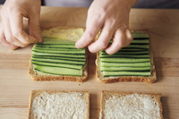 食パン4枚に、それぞれきゅうりを少しずつ重ねてずらしながら、すきまなく並べる。残りの食パンをそれぞれ重ね、手のひらで押さえてなじませる。1組ずつラップでぴっちりと包み、冷蔵庫で10分ほどやすませる。