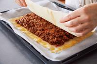 天板にのせた皮の周囲2cmくらいに、溶き卵を薄く塗り、内側に【1】のたねをのせて広げる。4層にした皮をのせ、縁を指で押さえてしっかり閉じ、角をつまんで密着させる。残りの溶き卵を表面に塗り、中央に長さ5cmほどの切り込みを十字に入れる。オーブンの下段に入れ、200℃で15分焼く。
