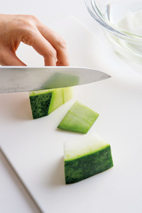 とうがんはわたと種を除き、縦4つ割りにして、横に幅4cmに切る。包丁で皮を厚めに切り落とし、縦半分に切って水にさらす。
