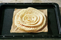 オーブン用シートごと天板にのせ、190℃のオーブンで25分ほど焼く。りんごの縁が乾いて焼き色がついたら、いったん取り出す。向きを変えてさらに3~5分焼く。フライ返しで持ち上げ、パイの裏側を見て、焼き色がついていたら焼き上がり。シートごとケーキクーラーにのせ、粗熱を取る。